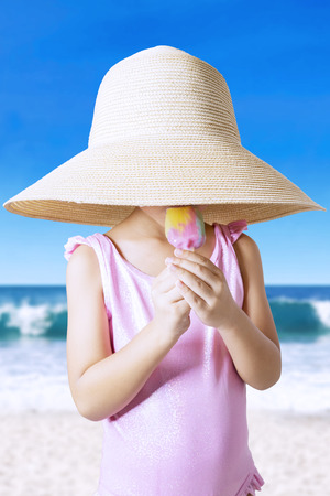 petite fille maillot de bain: Petite fille portant un grand chapeau et maillot de bain sur la plage, manger des glaces