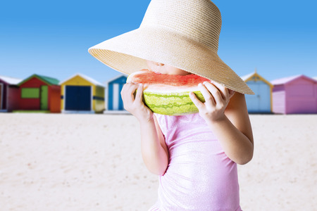 child swimsuit: Little child wearing swimsuit and a big hat on the shore while holding and eating a fresh watermelon