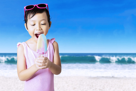 little girl swimsuit: Beautiful little girl wearing swimsuit with sunglasses, standing on the seaside while eating ice cream Stock Photo