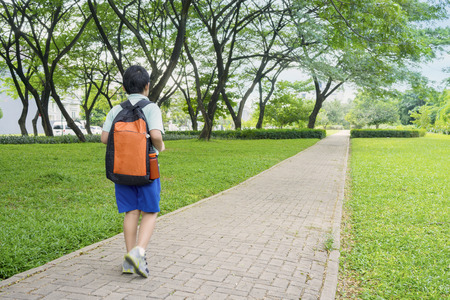 school uniforms: Rear view of male elementary school student walking alone to school while carrying backpack