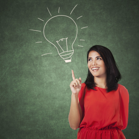 Atraktivní mladá žena s ležérní oblečení ukazuje na obraz lampy na tabuli. Koncepce najít myšlenku