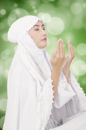 femmes muslim: Jeune femme musulmane de prier le Dieu tout en portant des vêtements blancs, tourné avec bokeh