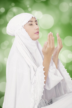 Muslim: Young muslim woman praying on the GOD while wearing white clothes, shot with bokeh background