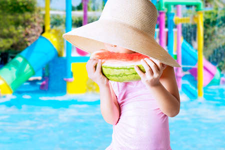 pink bikini: Closeup of female child wearing a big hat on the pool while eating a fresh watermelon