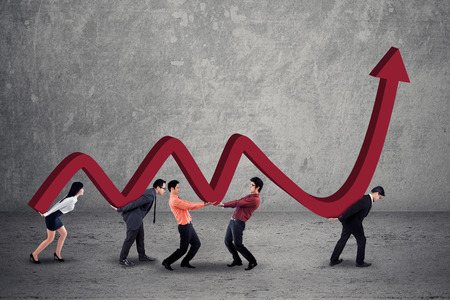 work group: Group of businesspeople work together to carry a business graph with upward arrow