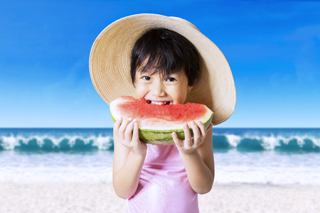 pink bikini: Pretty little child standing on the beach while eating a watermelon and wearing hat