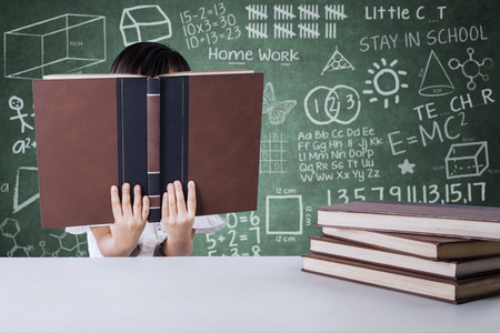 face shot: Little girl reading textbooks in the class while covering her face, shot with doodle background on the blackboard Stock Photo