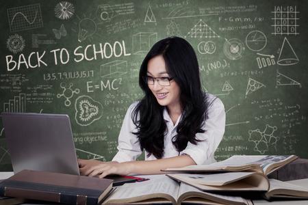 cabello negro: Retrato de estudiante adolescente con el pelo negro que estudia en la clase durante el uso de un ordenador portátil