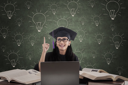 uni: Happy female graduate pointing her finger to express her idea on lamps drawing background Stock Photo