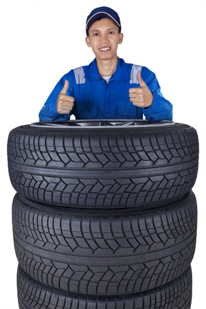 car shop: Young mechanic with a blue uniform and a heap of black tires, showing thumbs up at the camera Stock Photo
