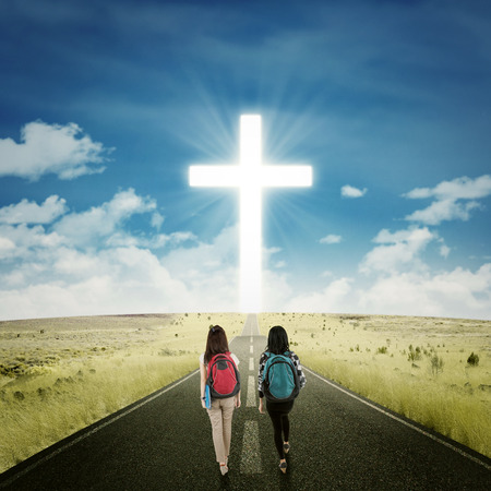 christian women: Back view of female students walking on the highway toward a cross on the end of the road Stock Photo