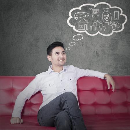 hombre pensando: Retrato de hombre joven sentado en el sofá, mientras que la planificación de su futuro