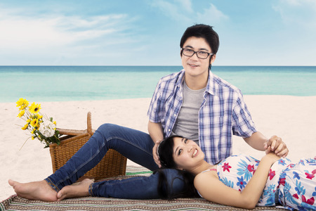beach mat: Beautiful asian couple relaxing at beach while sitting on mat and smiling at the camera Stock Photo