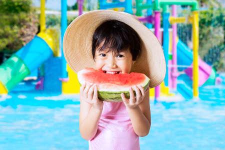 niños comiendo: Niña hermosa que come una sandía fresca en la piscina mientras usa un gran sombrero y traje de baño