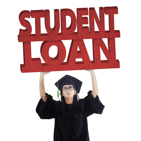 education loan: Female graduate student standing in the studio while wearing graduation cloak and holds student loan text Stock Photo
