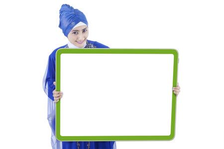 fille arabe: Jolie jeune femme musulmane avec des vêtements islamiques montrant un plateau vide, isolé sur fond blanc