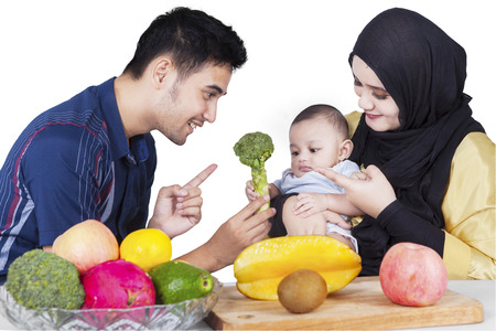 muslim baby: Young father with his wife in the kitchen showing broccoli and healthy food on their baby