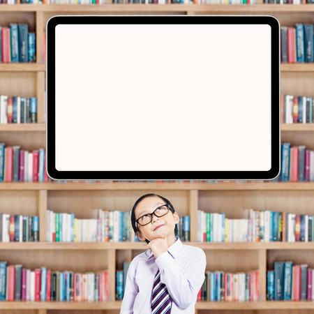 biblioteca: Niño pequeño pensativo que se coloca en la biblioteca, mientras que mirando a la tarjeta vacía Foto de archivo