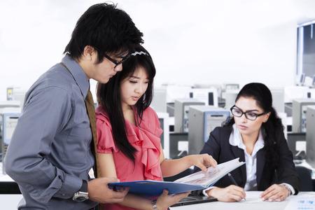 jovenes empresarios: Dos j�venes empresarios discutiendo un documento de negocios, mientras que su amigo que trabaja en el escritorio. Concepto de ocupado empresarios Foto de archivo