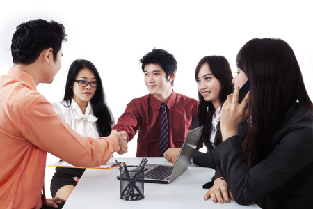 estar de acuerdo: Retrato de empresarios acuerdan cooperar y simbolizado por dar la mano en una reunión