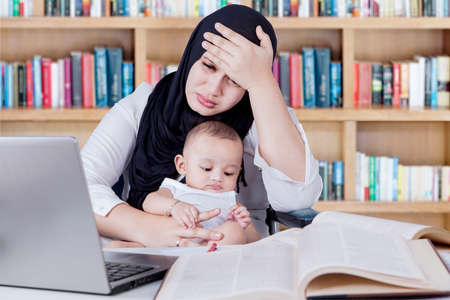 madre trabajando: Portrait of frustrated mother carrying her baby while working with laptop and textbooks in library Foto de archivo