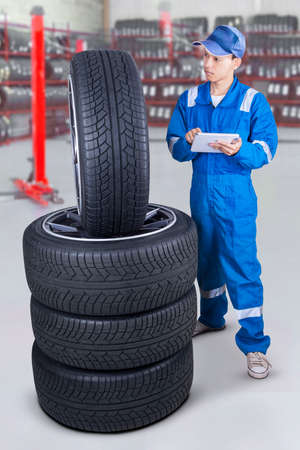 japanese people: Portrait of young mechanic wearing blue uniform and using a digital tablet to check tires at workshop