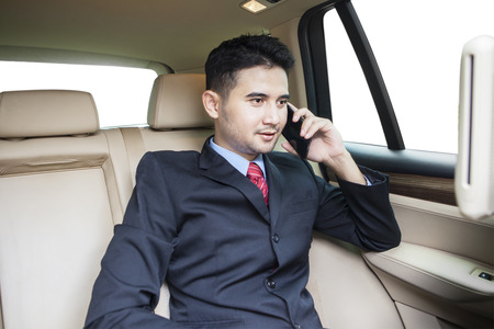 cellular: Portrait of businessman with formal suit, talking on the phone in the car