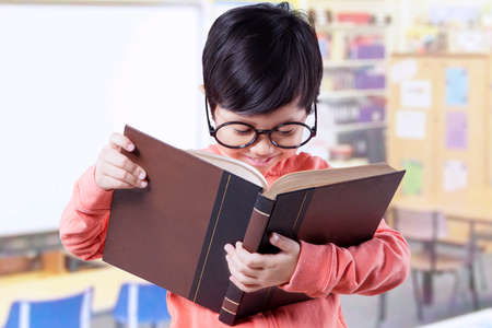 person reading: Portrait of pretty little student wearing glasses in the classroom and reading a literature Stock Photo