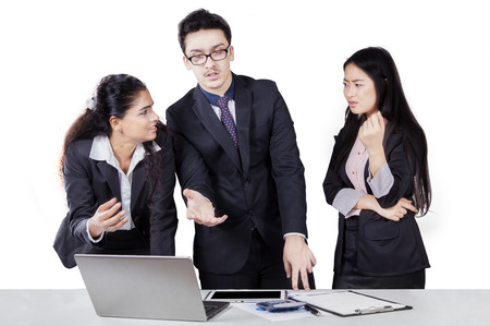debating: Portrait of three multi ethnic businesspeople in discussion and debating with laptop, isolated on white