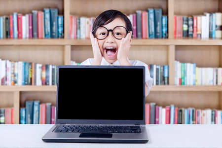 kids laptop: Portrait of attractive elementary school student with empty laptop screen, screaming in the library