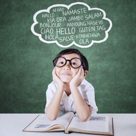bambini pensierosi: Bambina premurosa studio multi lingua con un libro e immaginare parole straniere