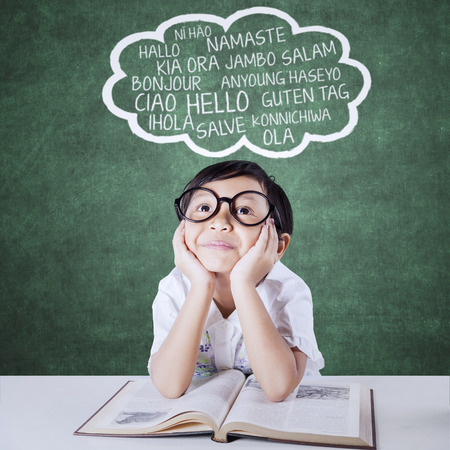 languages: Niña pensativa estudiando multi idioma con un libro e imaginar las palabras extranjeras