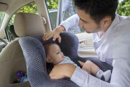 safety: Portrait of young man putting his newborn baby on the car seat Stock Photo