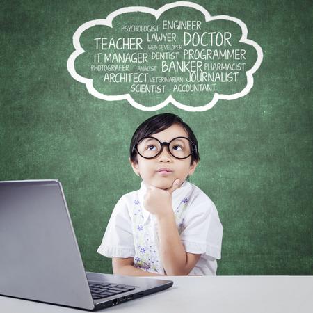 bambini pensierosi: Bella bambina con il computer portatile sul tavolo, il pensiero e immaginare i suoi sogni sulla bolla nuvola