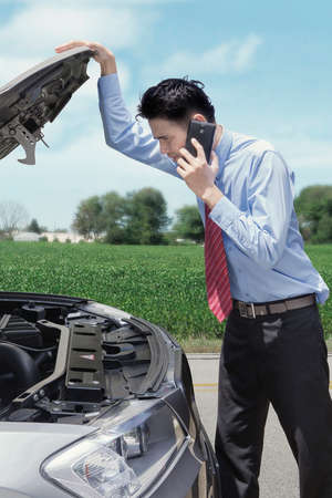 problem: Young businessman standing on the road while looking at the broken car, calling mechanic with his phone