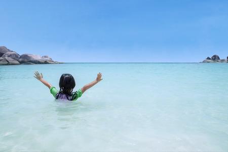 traje de bano: Vista trasera de la pequeña natación chica y jugando solo en la hermosa playa Foto de archivo