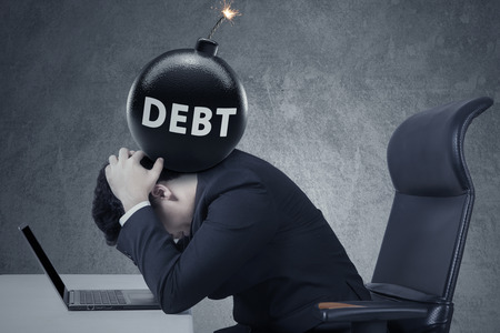 debt management: Concept of business debt deadline. Stressful businessman with laptop and a bomb of debt on his head