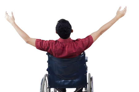 Rear view disabled person celebrate his freedom while sitting on wheelchair and raise hands up, isolated on white