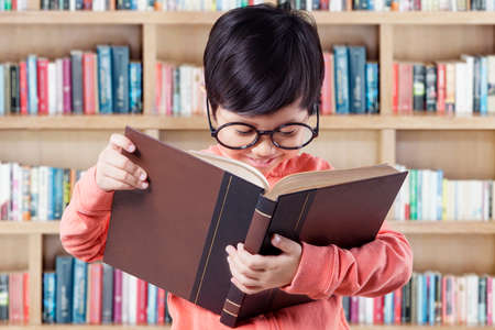 woman  glasses: Portrait of little girl with casual clothes and wearing glasses, reading a book in the library