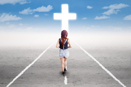 jesus in heaven: Rear view of young girl doing a spiritual journey by following a cross on the road