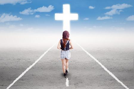 cielo: Vista posterior de la chica joven que hace un viaje espiritual siguiendo una cruz en el camino