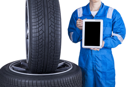 service occupation: Closeup of male mechanic showing empty tablet screen near tires, isolated on white background