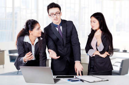 debating: Three businesspeople working together in a meeting with laptop and debating in the office