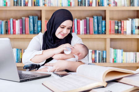 nursing bottle: Multitasking young mother nursing her baby with milk from bottle while working in the library