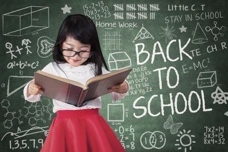 preescolar: Niña preescolar asiática volver a la escuela y leer un libro en el aula en serio Foto de archivo