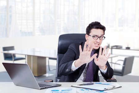 scolded: Caucasian worker with scared expression working in the office laptop and business document on the table Stock Photo