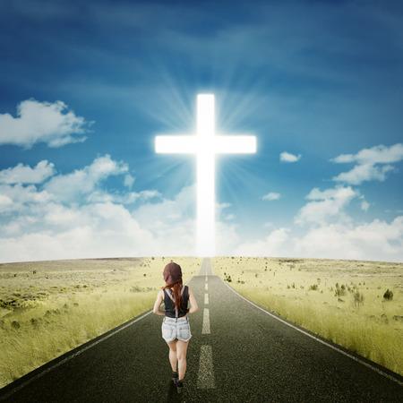 heaven: Vista trasera de la ocasional adolescente caminando por el camino hacia una cruz en la final de la carretera Foto de archivo