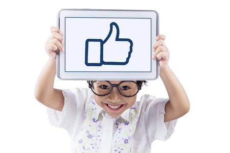 ok icon: Cute child smiling on the camera while holding a tablet to show a thumb up icon, isolated on white background