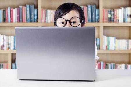personas de espalda: Ni�a con gafas y mira a escondidas en la c�mara de la parte posterior de la computadora port�til en el escritorio, un disparo en la biblioteca
