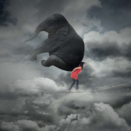 heavy risk: Portrait of woman carrying heavy elephant while walking on the rope
